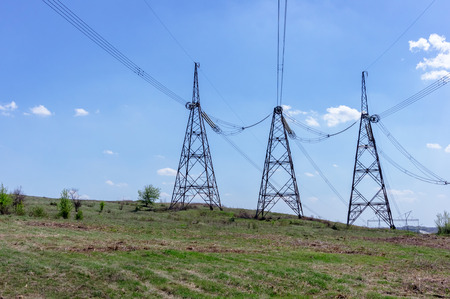 High-voltage power lines in green field against blue sky with white clouds 版權商用圖片
