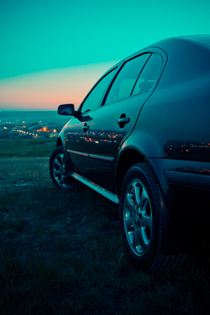 Black car in the field at night.