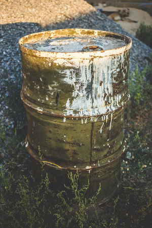 Dirty green metal barrel in the countryside.