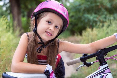 Little cute girl in a pink helmet near a bicycle in summer