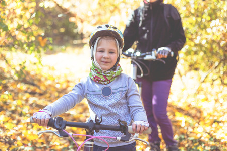 Little girl in the helmet with the bicycle in the autumn forest. 免版税图像
