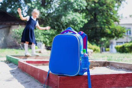Back to school concept. A school backpack in the foreground and a junior schoolgirl on the playground in the background. Accent photos on a school backpack.