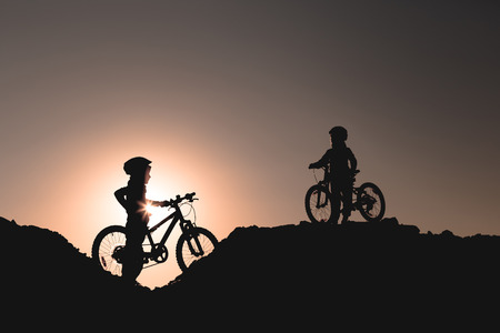 Silhouette of two little girls with bicycles at sunset. Stockfoto