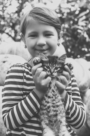 Cute little girl with kitten. Old monochrome style photo. 写真素材