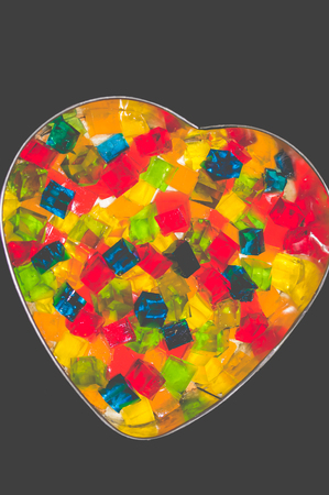Jelly cake in the form of a heart with multi-colored cubes in the middle. The cake is being prepared Фото со стока