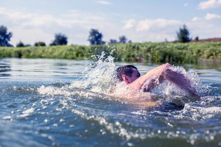 Der junge Mann schwimmt im Fluss. Standard-Bild