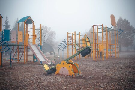 Empty childrens playground on a foggy autumn morning. Stok Fotoğraf