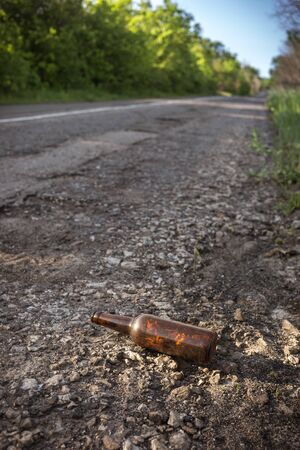 Beer bottle by the road. Environmental pollution concept