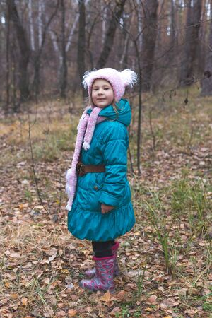 Little cute girl in the forest at autumn time.