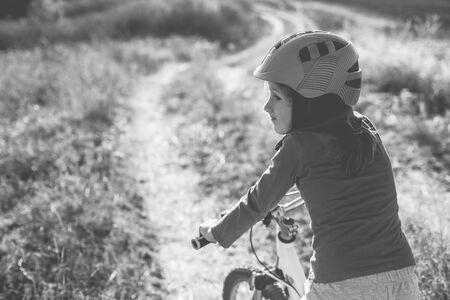 Little girl on a bike wearing a helmet on a dirt road in the field. Old monochrome photo.