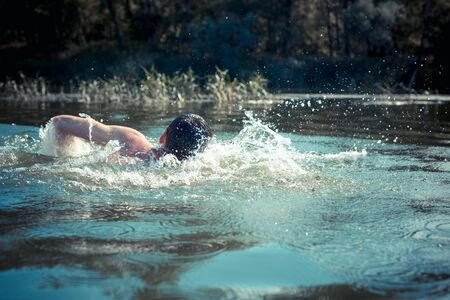 The young man swimming in the river.