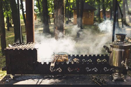 Barbecue with a samovar and grilled meat in nature.