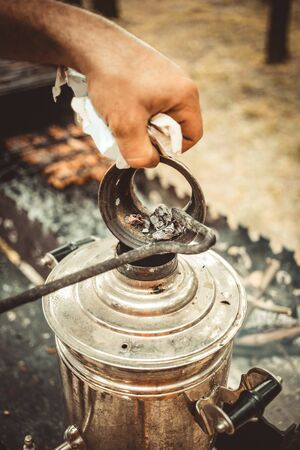 Man puts coals into a samovar.