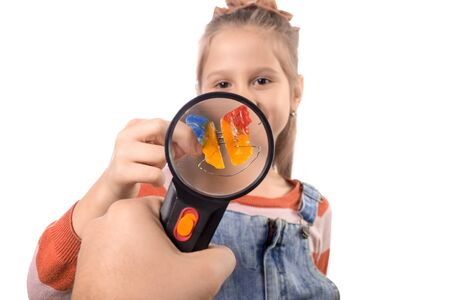 Portrait of a little cute girl with an orthodontic appliance on a white background through a magnifier.