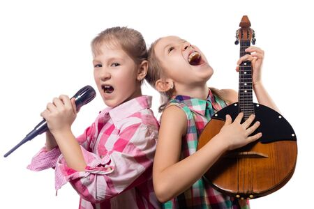 Two cute little girls posing with a microphone and domra. Concept of musician and vocalist. Studio photo on a white background. Stock Photo