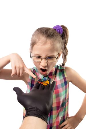 The reaction of a little girl to the proposal to wear an orthodontic appliance. Studio photo isolated on white background.
