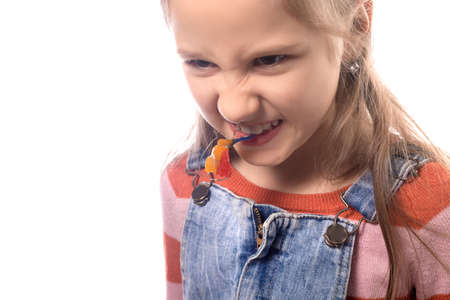 Portrait of little girl with orthodontics appliance isolated on white background.