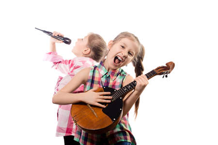 Two cute little girls posing with a microphone and domra. Concept of musician and vocalist. Studio photo on a white background.