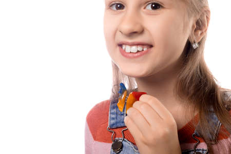 Little girl with orthodontics appliance isolated on white background.