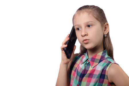 Cute little girl is talking on a cell phone. Studio photo on a white background.