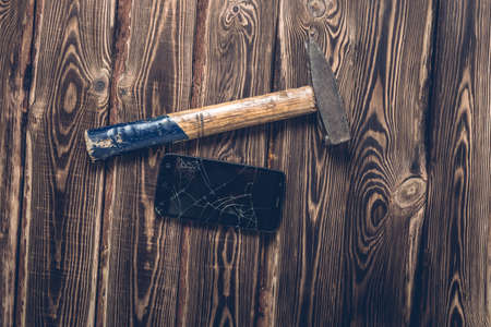 Old big hammer and broken smartphone on a wooden background. Studio photo.