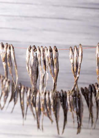 Small dry fish on a rope on a wooden background. Studio photo. Zdjęcie Seryjne