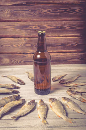 Dried perch and brown glass beer bottle on white wooden background. Studio photo.