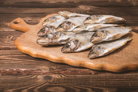 Dried fish on a wooden background. Studio photo.