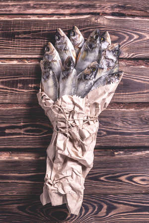 Beautiful dried fish in a paper bag on a wooden table. Studio photo.