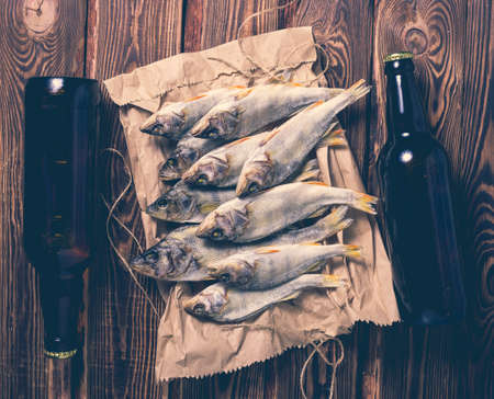 Beer bottles and dried fish on a paper bag on a wooden table. Studio photo. Zdjęcie Seryjne