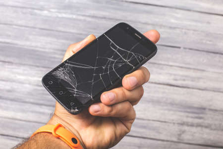 Broken black smartphone in hand on a white background. Studio photo for design