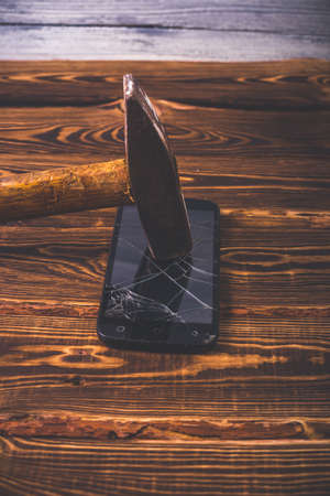 Old big hammer on a broken smartphone display. Studio photo on a wooden background. Zdjęcie Seryjne