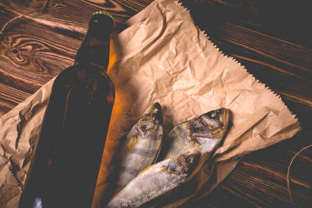 A bottle of beer and dried fish on a paper bag on a wooden table. Studio photo. Zdjęcie Seryjne