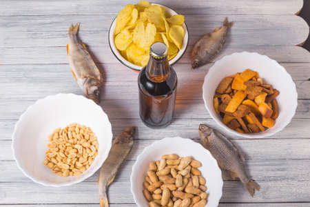 On a wooden table a bottle of beer, dried fish, chips, crackers and nuts. Studio photo. Zdjęcie Seryjne