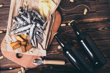 Brown glass bottles of beer and dried fish with chips, nuts, crackers on paper on a wooden background. Studio photo.