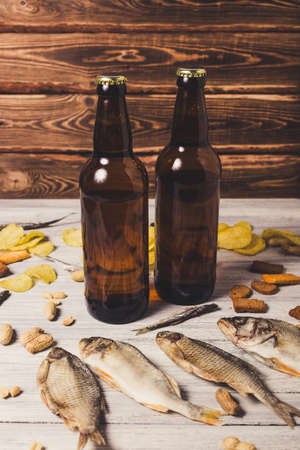 Brown glass bottles of beer and dried fish with chips, nuts, crackers on paper on a white wooden background. Studio photo.