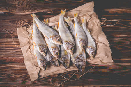 Beautiful dried fish on a paper bag on a wooden table. Studio photo.