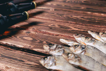 Brown bottles with beer and dried fish on a wooden table. Studio photo.