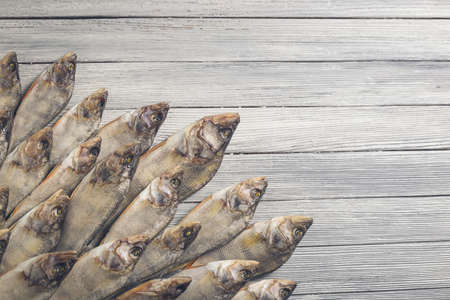 Dried perch on a white wooden background. Studio photo.