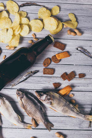 Brown glass bottle of beer and dried fish with chips, nuts, crackers on paper on a white wooden background. Studio photo. Zdjęcie Seryjne