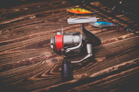 Studio photo of fishing tackle on a wooden background. A rod, a reel with a line and three wobblers. Photo with vignetting