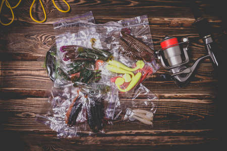Spinning rod with a reel and silicone baits in plastic bags. Studio photo on a wooden background. Flat lay Archivio Fotografico