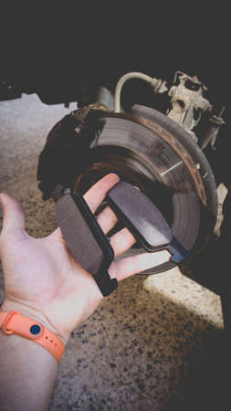 A man's hand with new brake pads on the background of a car without a wheel. Service work on replacing the front brake pads. Photo in the old style with vignetting.