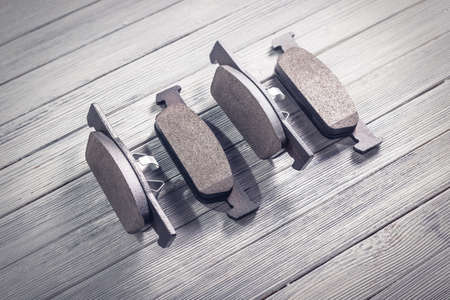 Studio photo of new car brake pads on a white wooden background. Photo with vignetting