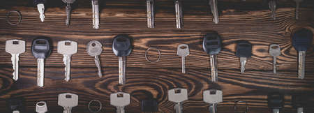 Studio photo of different keys on a wooden background. Photo in the old style with vignetting.