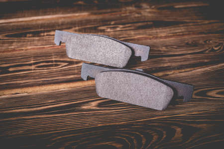 Studio photo of new black car brake pads on a wooden background.