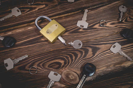 Studio photo of a lock with a broken key in it on a wooden background. Lots of other new keys around the lock. Photo in the old style with vignetting.