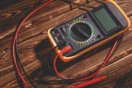 Multimeter and two test leads on a wooden background. A studio photo with hard lighting. Standard-Bild