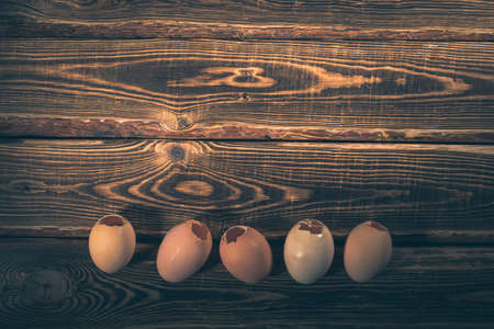 Empty chicken eggs with a hole on a wooden background. A studio photo with hard lighting. Standard-Bild