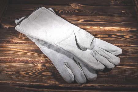 White leather welder gloves on a wooden background. A studio photo with hard lighting. Standard-Bild